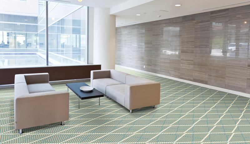 Geometric QuickWeave Brintons carpet in soft grey and cream tones with sofa and table in reception area